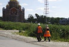 Δύο εργαζόμενοι στις πορτοκαλιές φόρμες είναι πίσω από το μεσημεριανό γεύμα στοκ εικόνες