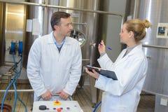 Δύο εργαζόμενοι στο labcoat που λειτουργεί στο εργοστάσιο στοκ φωτογραφία