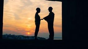 Δύο εργαζόμενοι συζητούν ένα πρόγραμμα, που στέκεται για ένα υπόβαθρο ηλιοβασιλέματος, πίσω άποψη απόθεμα βίντεο