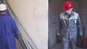Δύο εργαζόμενοι φέρνουν τα οικοδομικά υλικά σε ένα εργοτάξιο οικοδομής φιλμ μικρού μήκους
