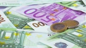 Δύο ευρο- νομίσματα πέρα από την περιστροφή υποβάθρου τραπεζογραμματίων απόθεμα βίντεο