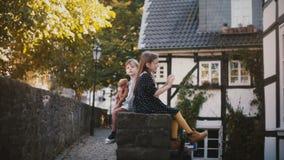 Δύο ευρωπαϊκά παιδιά κάθονται μαζί πλάτη με πλάτη Ο αδελφός και η αδελφή έχουν τη διασκέδαση μια ηλιόλουστη ημέρα Διαφορετικές πρ φιλμ μικρού μήκους