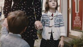 Δύο ευρωπαϊκά παιδιά μαζί με τη μητέρα κρατούν τα χέρια Ήρεμη και σοβαρή στάση αγοριών και κοριτσιών κοντά στο mom Πυροβοληθε'ν τ απόθεμα βίντεο
