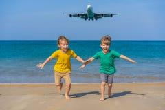 Δύο ευτυχή αγόρια έχουν τη διασκέδαση στην παραλία προσέχοντας τα προσγειωμένος αεροπλάνα Ταξίδι σε ένα αεροπλάνο με την έννοια π στοκ εικόνα με δικαίωμα ελεύθερης χρήσης