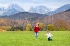 Δύο ευτυχή γελώντας παιδιά στον τομέα μεταξύ των βουνών Στοκ Φωτογραφία