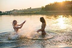 Δύο ευτυχή λεπτά νέα κορίτσια που καταβρέχουν στη λίμνη Στοκ φωτογραφία με δικαίωμα ελεύθερης χρήσης