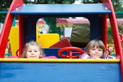 Δύο ευτυχή εύθυμα κορίτσια που κάθονται στο παιχνίδι αυτοκινήτων Στοκ εικόνες με δικαίωμα ελεύθερης χρήσης