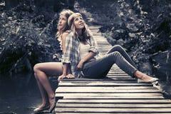 Δύο ευτυχή κορίτσια εφήβων που κάθονται στη γέφυρα στο θερινό δάσος στοκ φωτογραφίες με δικαίωμα ελεύθερης χρήσης