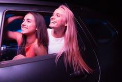 Δύο ευτυχή κορίτσια κοιτάζουν έξω από το αυτοκίνητο Φαίνονται απλοί και χαμογελούν Η ξανθή τρίχα κυματίζει Είναι στοκ εικόνες