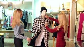 Δύο ευτυχή κορίτσια που εξετάζουν τα ενδύματα σε ένα μανεκέν σε ένα κατάστημα ιματισμού απόθεμα βίντεο