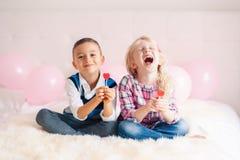 δύο ευτυχή λευκά καυκάσια χαριτωμένα λατρευτά αστεία παιδιά που τρώνε την καρδιά που διαμορφώνεται lollipops στοκ εικόνα