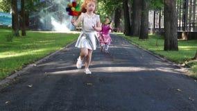 Δύο ευτυχή μικρά κορίτσια που οργανώνονται με τους ανεμόμυλους στο πράσινο θερινό πάρκο απόθεμα βίντεο