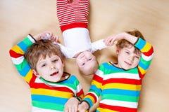 Δύο ευτυχή μικρά προσχολικά αγόρια παιδιών με το νεογέννητο κοριτσάκι Στοκ Φωτογραφία
