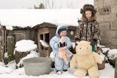 Δύο ευτυχή παιδιά το χειμώνα διαμορφώνουν τα ενδύματα οδηγούν ένα έλκηθρο με έναν χοίρο παιχνιδιών και μια αρκούδα σε μια γέφυρα  Στοκ Φωτογραφία