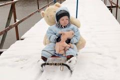 Δύο ευτυχή παιδιά το χειμώνα διαμορφώνουν τα ενδύματα οδηγούν ένα έλκηθρο με έναν χοίρο παιχνιδιών και μια αρκούδα σε μια γέφυρα  Στοκ Εικόνα