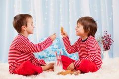 Δύο ευτυχή παιδιά που τρώνε τα μπισκότα στα Χριστούγεννα και το πόσιμο γάλα στοκ φωτογραφία