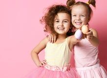 Δύο ευτυχή χαμογελώντας κορίτσια παιδιών καταδεικνύουν τα χρωματισμένα αυγά την ημέρα Πάσχας στοκ εικόνα