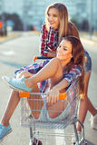 Δύο ευτυχή όμορφα κορίτσια εφήβων που οδηγούν το κάρρο αγορών υπαίθρια Στοκ Φωτογραφία