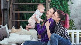 Δύο ευτυχείς ίδιοι γονείς φύλων που χαμογελούν το παιχνίδι με λίγη κόρη νηπίων που απολαμβάνει το Σαββατοκύριακο απόθεμα βίντεο