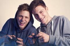 Δύο ευτυχείς αδελφοί που παίζουν τα τηλεοπτικά παιχνίδια και το γέλιο στοκ εικόνες με δικαίωμα ελεύθερης χρήσης
