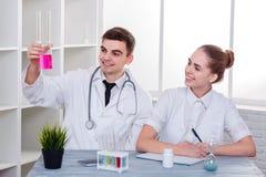 Δύο ευτυχείς γιατροί σε ομοιόμορφο, ένας τύπος και ένα κορίτσι, κάθονται στο γραφείο και εξετάζουν το ρόδινο υγρό σε μια φιάλη γυ στοκ φωτογραφίες με δικαίωμα ελεύθερης χρήσης