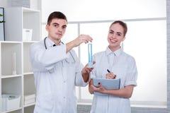Δύο ευτυχείς γιατροί, το κορίτσι γράφουν σε ένα σημειωματάριο, και ο τύπος κρατά μια μπλε-υγρή φιάλη στοκ φωτογραφία με δικαίωμα ελεύθερης χρήσης