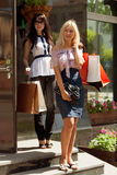 Δύο ευτυχείς γυναίκες με τις τσάντες αγορών στοκ εικόνες