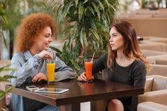 Δύο ευτυχείς γυναίκες που μιλούν και που πίνουν το χυμό στον καφέ Στοκ Εικόνες