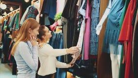Δύο ευτυχείς γυναίκες που ψωνίζουν στο κατάστημα ενδυμάτων απόθεμα βίντεο