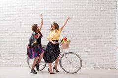 Δύο ευτυχείς γυναίκες στα θερινά φορέματα οδηγούν μαζί σε ετοιμότητα αναδρομικών ποδηλάτων και χειρονομίας προς τα εμπρός στοκ φωτογραφία