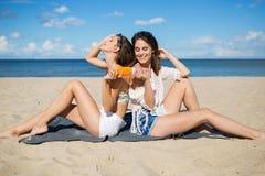 Δύο ευτυχείς γυναίκες στην παραλία που χρησιμοποιεί το suntan πετρέλαιο Στοκ Φωτογραφίες