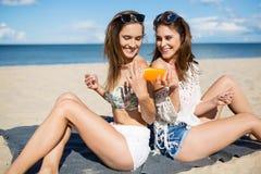 Δύο ευτυχείς γυναίκες στην παραλία που χρησιμοποιεί το suntan πετρέλαιο Στοκ εικόνες με δικαίωμα ελεύθερης χρήσης