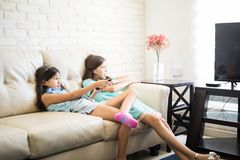 Δύο ευτυχείς ελκυστικοί αδελφές ή φίλοι κοριτσιών στον καναπέ στο hom Στοκ Φωτογραφίες