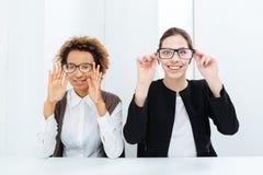 Δύο ευτυχείς επιχειρηματίες που έχουν τη διασκέδαση με τα γυαλιά στην αρχή Στοκ Εικόνες