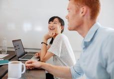 Δύο ευτυχείς επιχειρηματίες που κάθονται στη αίθουσα συνδιαλέξεων Στοκ φωτογραφία με δικαίωμα ελεύθερης χρήσης