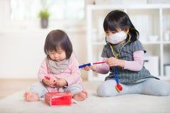 Δύο ευτυχείς ιαπωνικές αδελφές που παίζουν με το ιατρικό σύνολο στο σπίτι Στοκ Εικόνες