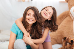 Δύο ευτυχείς καλές αδελφές που κάθονται και που αγκαλιάζουν στο σπίτι Στοκ εικόνες με δικαίωμα ελεύθερης χρήσης