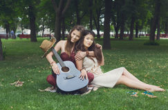 Δύο ευτυχείς κομψές μοντέρνες φίλες boho με την κιθάρα, πικ-νίκ Στοκ Εικόνες