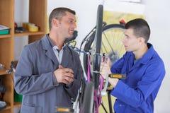 Δύο ευτυχείς μηχανικοί με τα εργαλεία στο σταθμό επισκευής ποδηλάτων Στοκ φωτογραφία με δικαίωμα ελεύθερης χρήσης