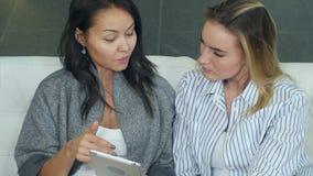 Δύο ευτυχείς νέοι θηλυκοί φίλοι χρησιμοποιούν το ψηφιακό PC ταμπλετών, που μιλά και που κάθεται στον καναπέ απόθεμα βίντεο
