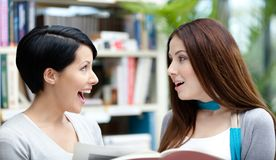Δύο ευτυχείς σπουδαστές που διαβάζονται στη βιβλιοθήκη Στοκ Φωτογραφία