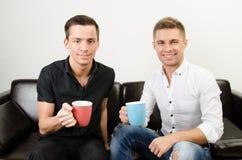 Δύο ευτυχείς τύποι πίνουν τον καφέ στοκ εικόνες
