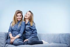 Δύο ευτυχείς φίλοι γυναικών που φορούν την εξάρτηση τζιν Στοκ εικόνα με δικαίωμα ελεύθερης χρήσης