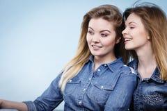 Δύο ευτυχείς φίλοι γυναικών που φορούν την εξάρτηση τζιν Στοκ Εικόνες