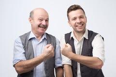 Δύο ευτυχείς φιλαράκοι που φορούν το πουκάμισο και τη φανέλλα που χαμογελούν και που παρουσιάζουν fis στοκ εικόνες