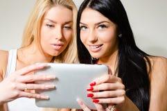 Δύο ευτυχείς όμορφες νέες γυναίκες που κοιτάζουν στο PC ταμπλετών και το χαμόγελο Στοκ Εικόνες
