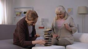 Δύο ευτυχείς ώριμες γυναίκες που παίζουν στο παιχνίδι φραγμών, ελεύθερος χρόνος στο οίκο ευγηρίας απόθεμα βίντεο