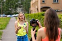 Δύο εφηβικές φίλες κοριτσιών, στην πόλη στη φύση το καλοκαίρι Σε την τα χέρια κρατούν ένα μπουκάλι νερό και ένα πράσινο μήλο στοκ εικόνες
