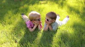 Δύο εύθυμα ευτυχή μικρά παιδιά βρίσκονται στη χλόη στα γυαλιά ηλίου το καλοκαίρι φιλμ μικρού μήκους