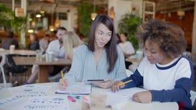 Δύο εύθυμα κορίτσια - ασιατικά και ο Μαύρος, που κουβεντιάζει και που εργάζεται μαζί στον καφέ απόθεμα βίντεο